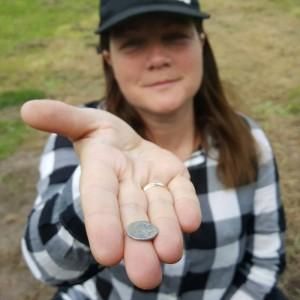 Louise Stahlschmidt med en romersk sølvmønt, en såkaldt denar, fundet med metaldetektor på jernalderbopladsen. Foto Nanna Stahlschmidt.
